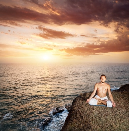 Man sitting by ocean