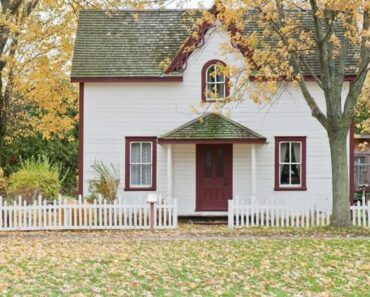homeowner,homeownership,real estate quaint white house with red trim and white picket fence