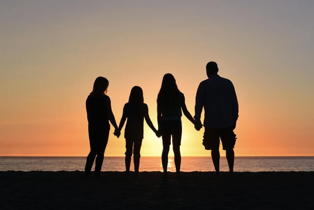 household formation family standing on the beach at sundown